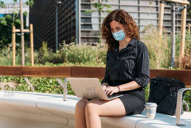 Business woman working on a park bench using her personal computer and wearing a protective mask.