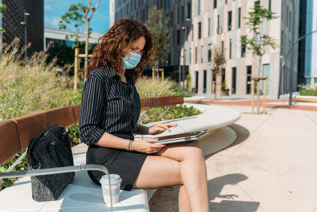 Business woman working on a park bench using her digital tablet during the corona virus pandemic.