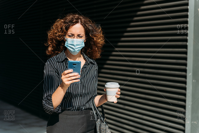 Busy woman walking on the street holding a coffee and using her cellphone. She's wearing a protective mask due to Covid-19.