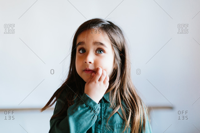 Little beautiful girl with big blue eyes looking away and touching face while standing on white background