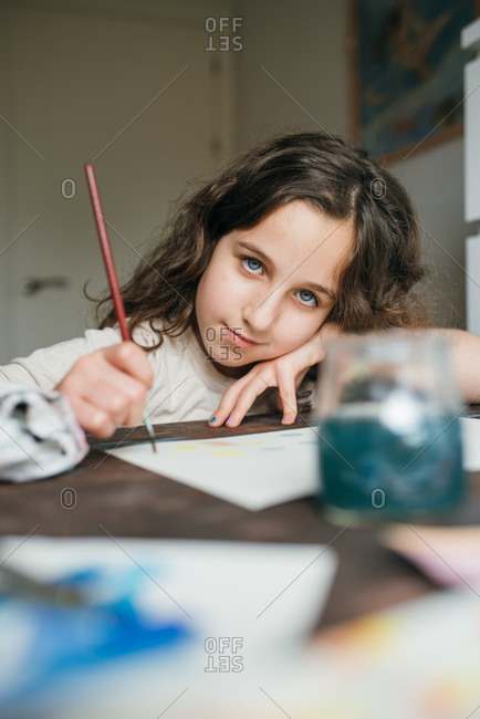 Adorable child sitting at table and creating painting with watercolor and paintbrush while looking at camera