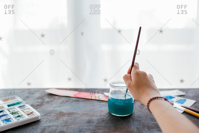 Unrecognizable little girl painter sitting at table and putting paintbrush in glass jar with colored water while painting in workshop