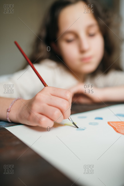 Blurred adorable focused child sitting at table and creating painting with watercolor and paintbrush while looking at camera