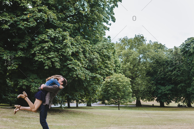 Side view of happy boyfriend holding girlfriend above ground while embracing in garden during weekend stroll