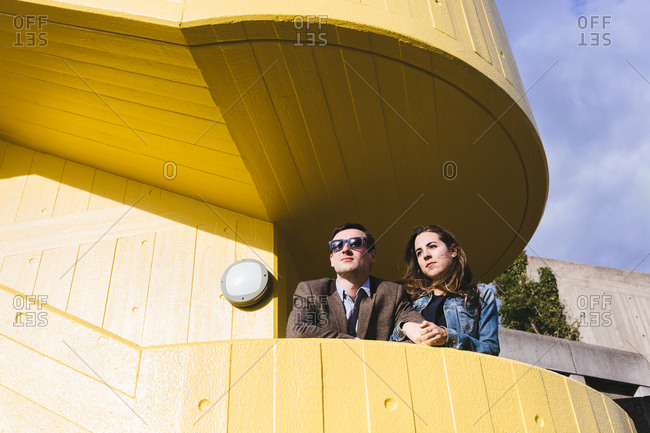 From below of stylish girlfriend and boyfriend standing close to each other on terrace of geometric building and looking away