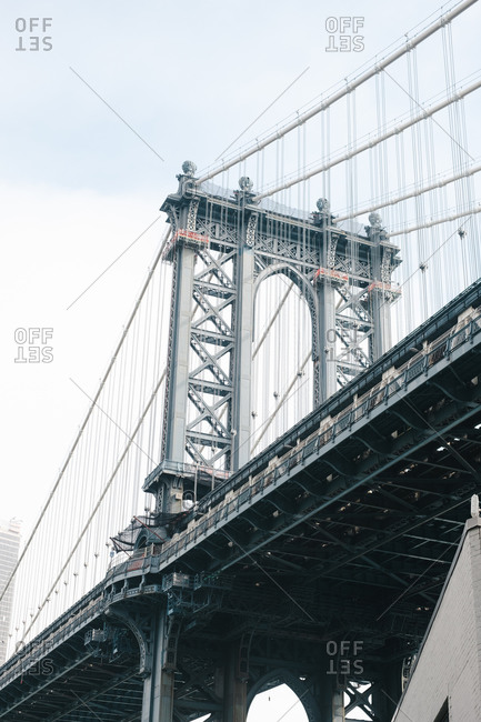 From below of Brooklyn bridge with metal cables and arched construction on background of cloudy sky
