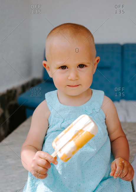 Cute toddler sitting on high chair on terrace and eating delicious popsicles while looking at camera