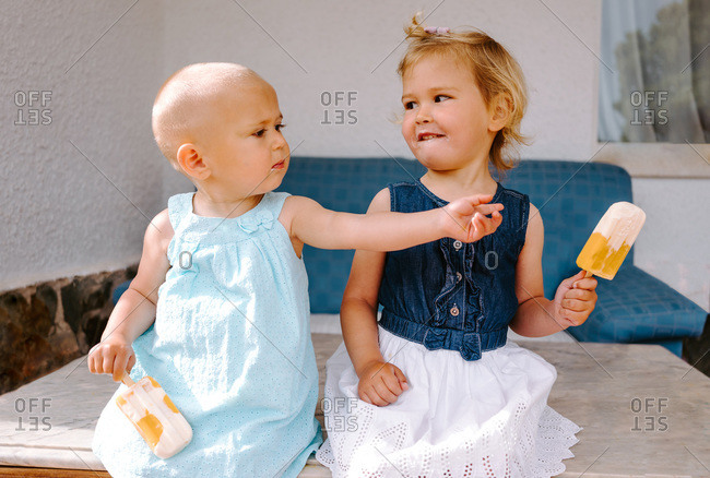 Cute little girls eating yummy popsicles while enjoying summer and sitting together in backyard