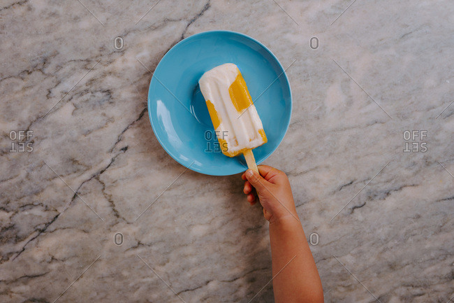 Top view of cropped unrecognizable kid hand grabbing a delicious fruit popsicle placed on table