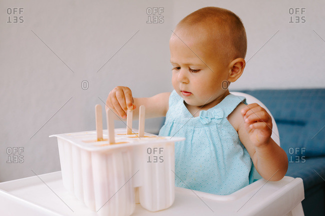 High angle of cute toddler sitting on high chair on terrace and eating delicious popsicles