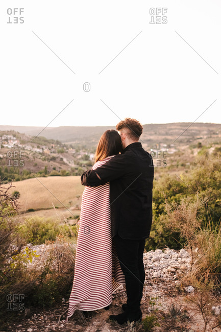 Back view of unrecognizable boyfriend hugging girlfriend covered with plaid while standing together on hill and admiring spectacular scenery on valley