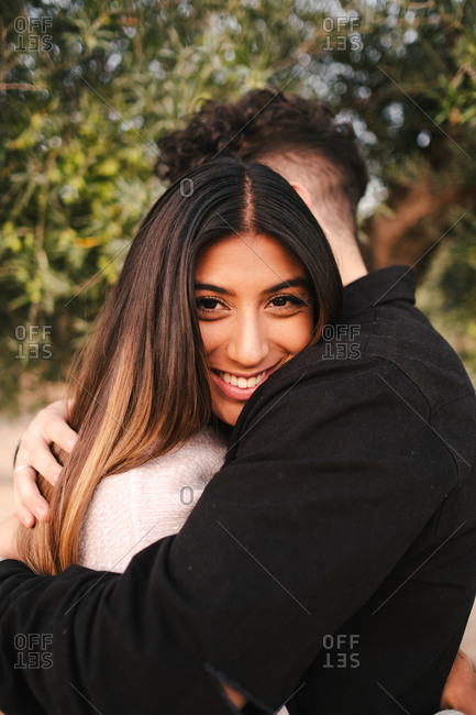 Side view of tender multiracial couple in stylish wear standing in green garden and embracing