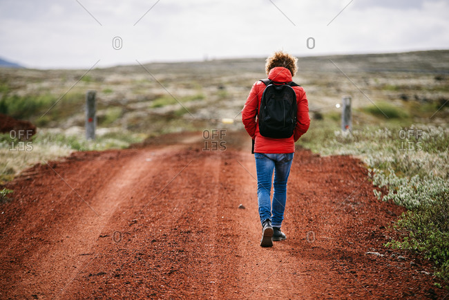 Back view of traveling man in outerwear walking along sandy road during vacation in Iceland