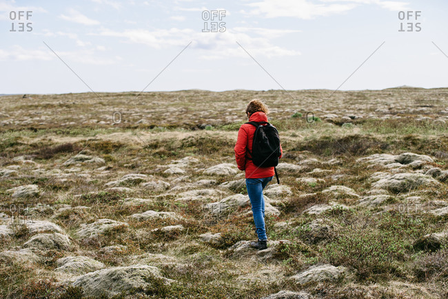 Back view of unrecognizable traveling man in outerwear and backpack walking rocky green meadow during vacation in Iceland