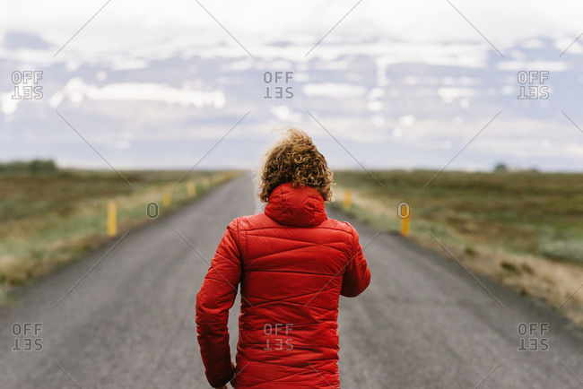 Back view of unrecognizable traveling man wearing warm clothes walking along empty asphalt roadway and enjoying scenery of mountains covered with snow in Iceland