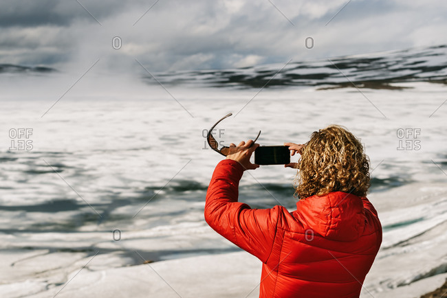 Back view of unrecognizable male tourist in outerwear taking picture of spectacular scenery of frozen lake on smartphone during vacation in Iceland on sunny day
