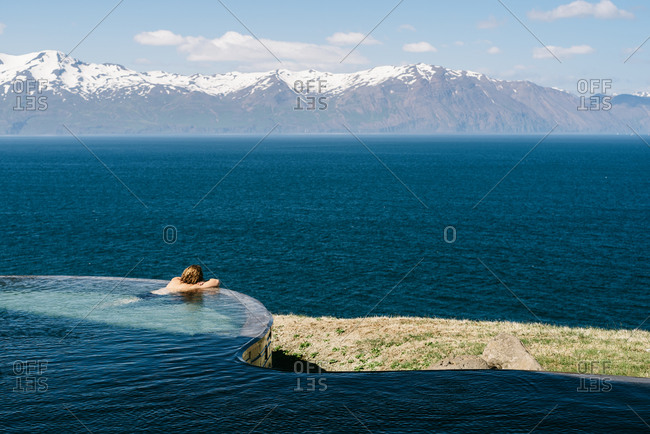 Back view of male tourist leaning on poolside and admiring majestic landscape of mountain ridge and tranquil sea
