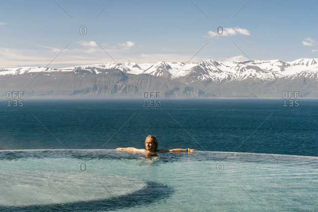 Side view of male tourist leaning on poolside and admiring majestic landscape of mountain ridge and tranquil sea