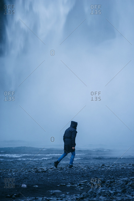 Back view of delighted unrecognizable male tourist in outerwear walking on background of waterfall while enjoying vacation in Iceland and looking at camera