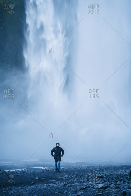 Delighted male tourist in outerwear walking on background of waterfall while enjoying vacation in Iceland and looking at camera