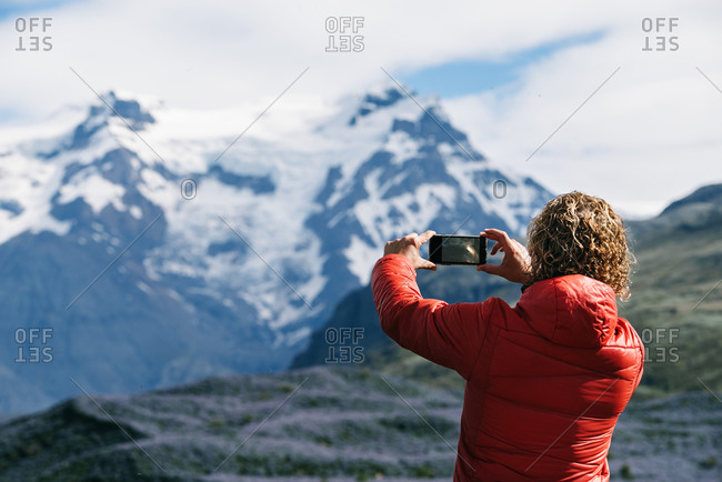 Back view of unrecognizable male tourist in warm clothes taking pictures of amazing mountain ridge while using cellphone camera and travelling around Iceland during vacation in winter