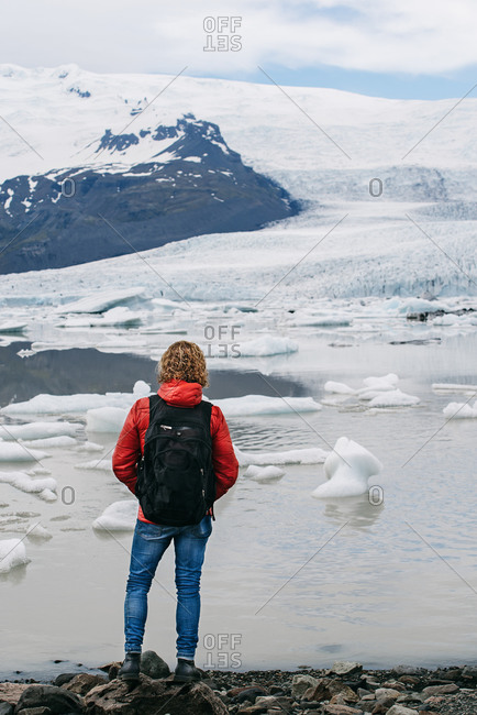 Back view of male tourist with backpack and in outerwear standing stony coast and admiring scenery of lake with ice