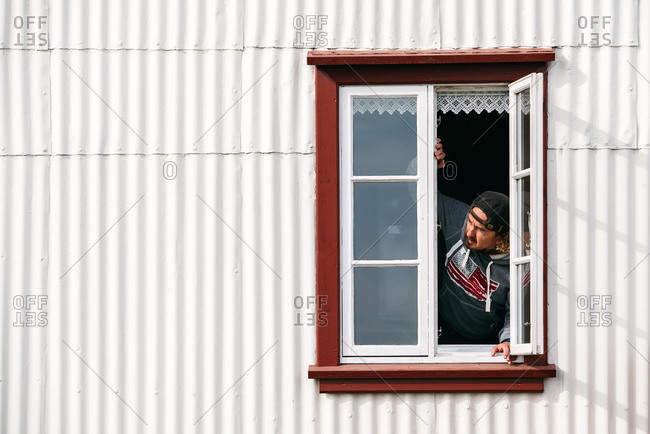 Male leaning on windowsill and looking out of window of residential building in countryside in Iceland