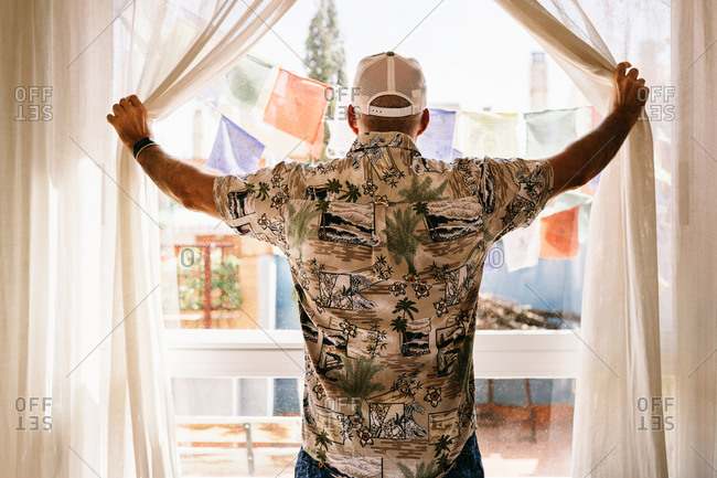 Back view of unrecognizable man in cap and shirt opening light curtains of window and looking in sunny yard