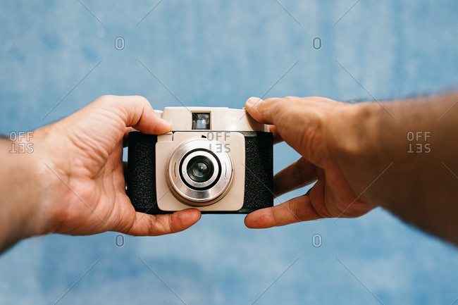 Cropped unrecognizable man hands taking picture with retro camera in light studio