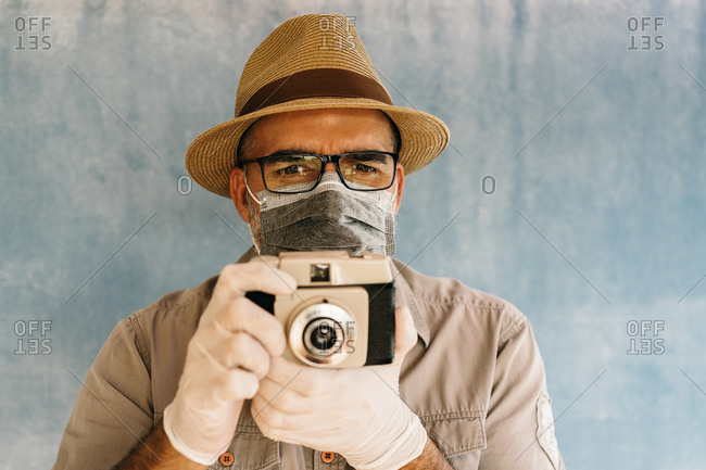 Middle aged man in latex gloves and medical mask taking picture with retro camera in light studio looking at camera
