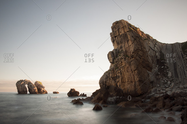 Long exposure landscape of sea water washing rough rocky cliff in sunny day