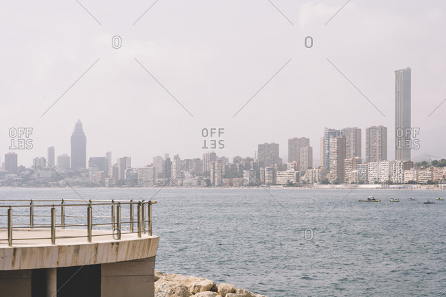 Skyline of Benidorm city with contemporary architecture seen from waterfront of sea in cloudy day in Spain
