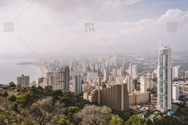 From above cityscape of densely built Benidorm city district with contemporary skyscrapers covered with haze in Spain
