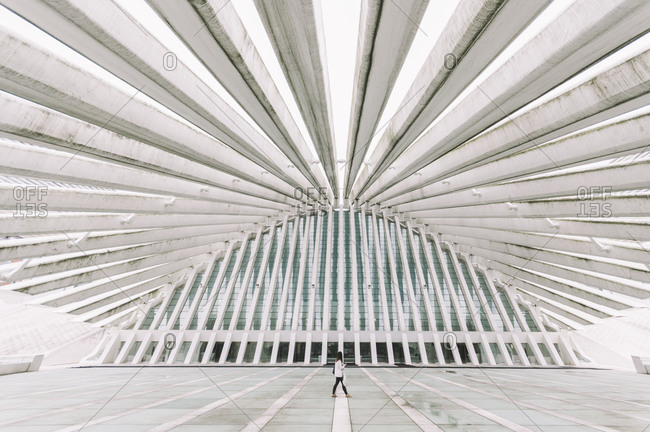 October 19, 2014: Anonymous person walking along modern curve shaped building of Oviedo Conference Center with futuristic design in Spain
