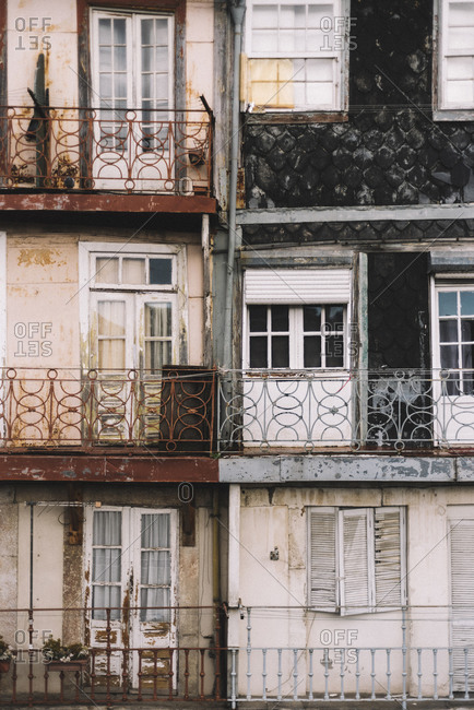 Textured background of exterior of aged house with weathered walls and balconies with metal railings
