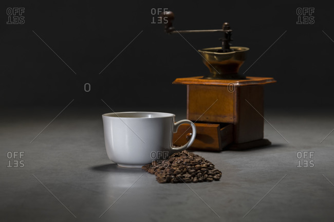 Fresh black coffee in white ceramic cup placed on saucer near coffee grinder and coffee beans on concrete table