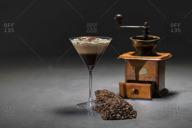 Roasted coffee beans and cocktail glass with yummy cappuccino with cream placed on concrete table near retro grinder