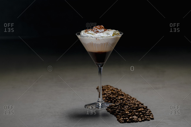 Roasted coffee beans and cocktail glass with yummy cappuccino with cream placed on concrete table