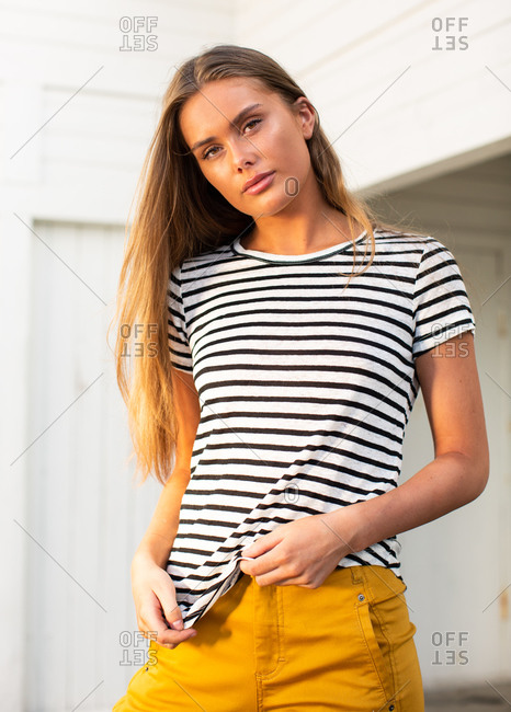 Calm female wearing trendy striped t shirt standing in port on background of wooden wall looking at camera