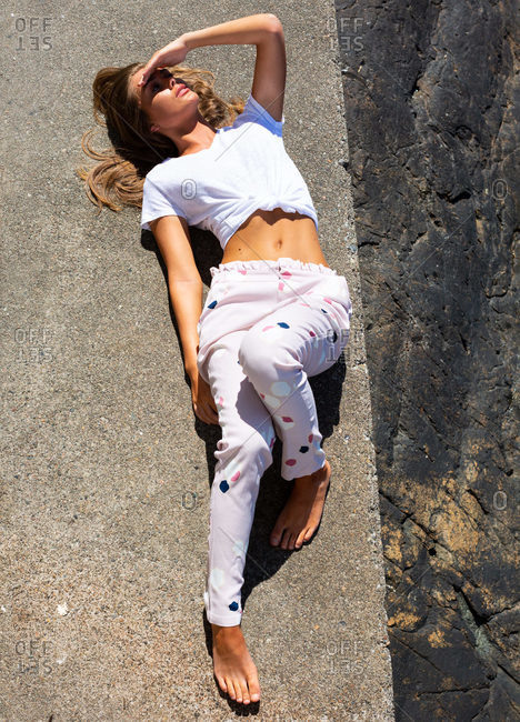 From above of slim female in casual wear lying on stone ground at waterfront while relaxing during summer vacation and looking away