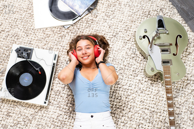 From above of happy young female looking at camera in casual wear lying on floor near guitar and listening to music with headphones and vinyl player while enjoying free time at home