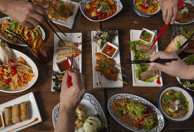 From above cropped unrecognizable people with chopstick eating assorted colorful spicy Thai food served for family dinner on wooden table