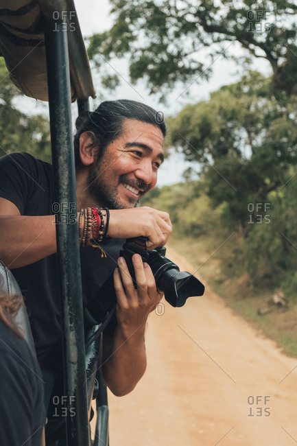 Happy traveling male with professional photo camera taking photos of wildlife during safari