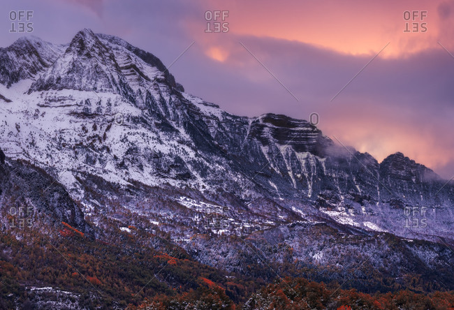 Snowy mountain ridge against cloudy sky on stormy day in autumn countryside
