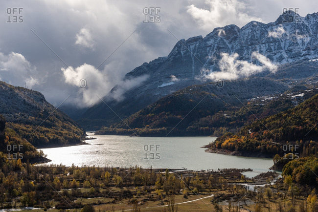 Lake close to snowy mountain ridge and cloudy sky in a landscape autumn