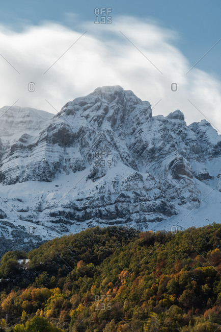 Picturesque view of snow mountains in forest on hill slope on cold autumn day in nature