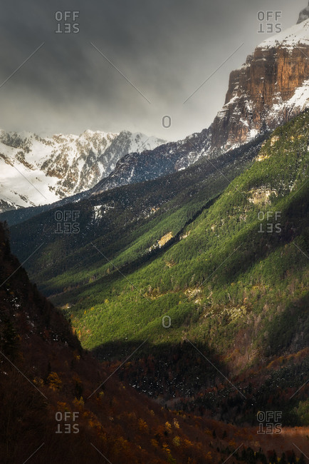 Green valley and snowy mountain ridge against gray cloudy sky on stormy day in countryside
