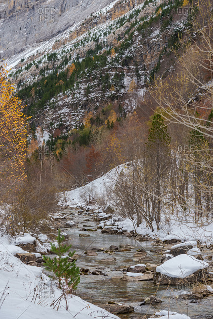 Fast stream with cold water flowing near mountain ridge covering with snow on autumn day in nature