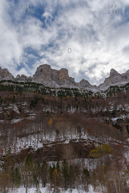 Forest and snowy mountain ridge against cloudy sky on stormy day in autumn countryside