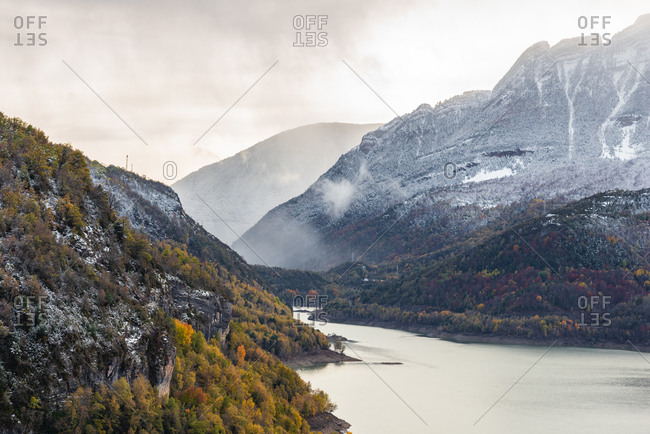 Lake and snowy mountain ridge with autumn tree located against overcast sundown sky in evening in nature